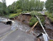 A felled tree lies across a road washed away by a rain-swollen river in Kristinehamn